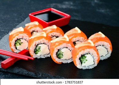 Philadelphia Maki Sushi made of Fresh Raw Salmon, Cream Cheese and Cucumber, Salmon sushi rolls on a wooden background, the highest quality for the menu and advertising
