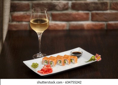Philadelphia maki sushi rolls with salmon, cheese cream, cucumber on white plate and glass of wine.