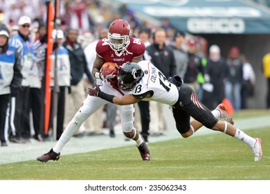 PHILADELPHIA - NOVEMBER 29: Temple Owls wide receiver Romond Deloatch (84) is hit hard near the sideline after a catch during the football game November 29, 2014 in Philadelphia.