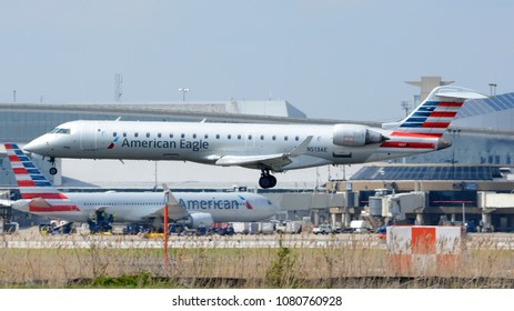 Philadelphia, PA - April 28th, 2018: An American Eagle CRJ700 operated by PSA Airlines lands at Philadelphia International Airport in front of Terminal A and an American Airlines A330