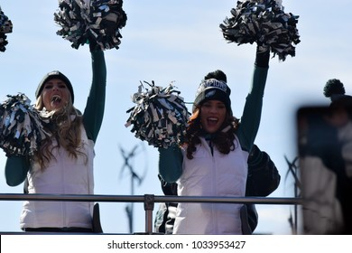 PHILADELPHIA, PA - February 8, 2018: two Eagles cheerleaders celebrate Super Bowl LII NFL world championship atop bus during parade down Broad Street
