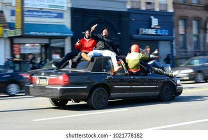 Philadelphia, PA - February 8th, 2018: A Group of People Sit on the Sides and Roof of a Moving Car on Broad Street while Celebrating after the Eagles Victory Parade