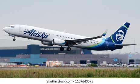 Philadelphia, PA - June 3rd, 2018: An Alaska Airlines Boeing 737-990ER Departing Philadelphia International Airport in Front of a Hangar
