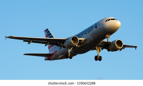 Philadelphia, PA - March 4th, 2019: An American Airlines A319-112 Landing, Illuminated by the Sunset