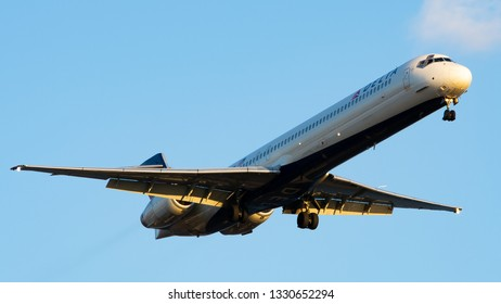 Philadelphia, PA - March 4th, 2019: A Delta Airlines McDonnell Douglas MD-90-30 Landing, Illuminated by the Sunset