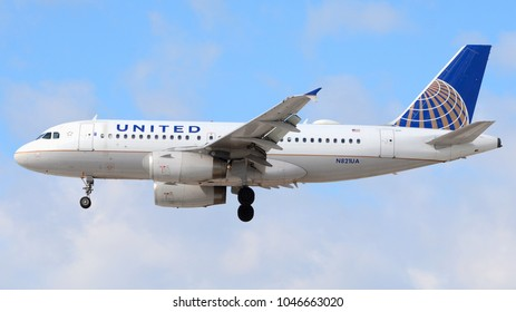 Philadelphia, PA - March 9th, 2018: A United Airlines Airbus A319-131 landing at Philadelphia International Airport in front of a Cloudy Sky