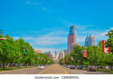 Philadelphia, PA / USA - 05 26 2014: Philly skyline and Philadelphia city hall view of the downtown with international flags from different countries from the Benjamin Franklin parkway on summer day