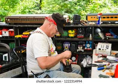 Philadelphia, PA / USA - 06-28-2013: Train engineer fixing a model train surrounded by collection of miniature rail cars.