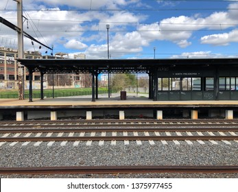 Philadelphia, PA / USA - April 15, 2019: Center City bound train platform at Septa North Philadelphia Station as seen from Trenton bound station side in middle of day with cloudy sky.