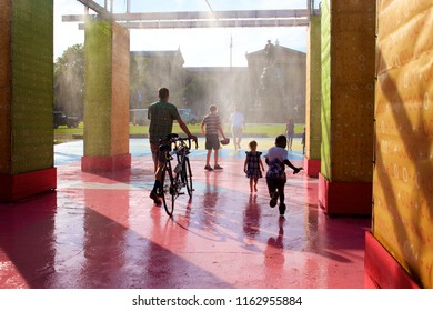 Philadelphia, PA USA - July 20, 2018: Crowds of people enjoy a misting station at The Oval+, a four-week summer event at Eakins Oval in Philadelphia, Pennsylvania.
