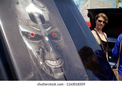 Philadelphia, PA, USA - July 29, 2018: A woman checks out a custom painted car hood on display at a vintage auto show in Philadelphia's East Passyunk neighborhood.