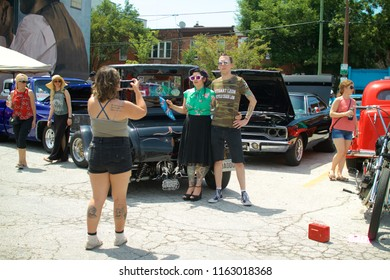Philadelphia, PA, USA - July 29, 2018: A hipster couple in retro dress pose for a photo at a vintage auto show in Philadelphia's East Passyunk neighborhood.