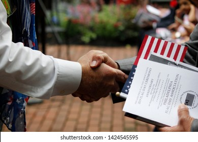 Philadelphia, PA / USA - June 14, 2019: A new United States citizen receives a warm handshake and congratulations during a special naturalization ceremony on Flag Day at the historic Betsy Ross House.