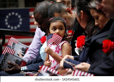 Philadelphia, PA / USA - June 14, 2019: The daughter of a immigrant holds an American flag while she joins her mother's naturalization ceremony on Flag Day at the historic Betsy Ross House.