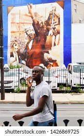 Philadelphia, PA / USA - June 17, 2019:  Local residents go about daily life at an intersection in West Philadelphia, where a memorial to Civil Rights leader, Dr. Martin Luther King Jr. is located.