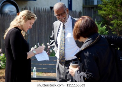 Philadelphia, PA, USA - June 7, 2018; State Senator Art Haywood (center) mingles with community members before the dedication of a new pocket park and Little Free Library in Northwest Philadelphia.