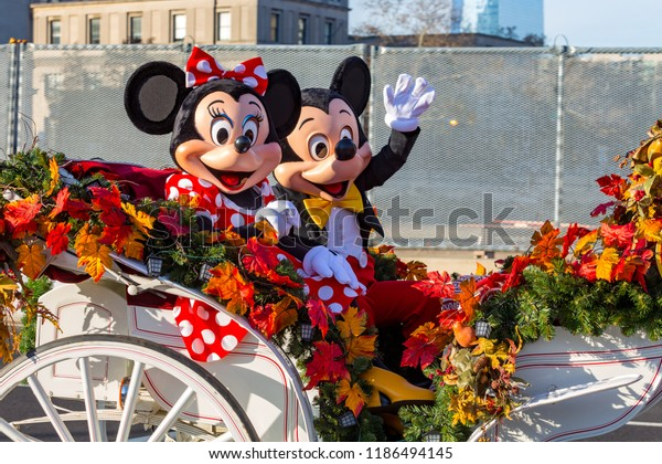 Mickey and Minnie Mouse ride in an open carriage
