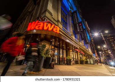 Philadelphia, PA--Feb 4, 2020; Time exposure captures blurred motion of customers entering and leaving front doors of Wawa convenience store downtown in winter at night.