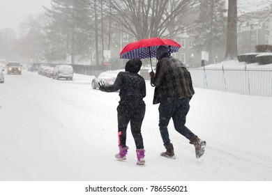 Philadelphia, PA/USA - January 4, 2018: A couple with a red umbrella braves icy gusts as area residents brace for the January 4, 2018 'Bomb Cyclone' winter storm, in Northwest Philadelphia.