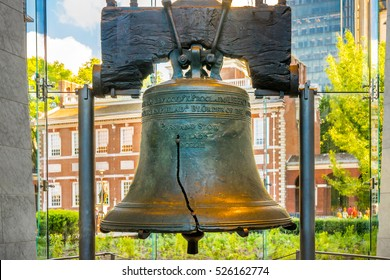 PHILADELPHIA, PENNSYLVANIA, USA - JUNE 30, 2016: Liberty Bell in the Liberty Bell Center in Independence National Historical Park with sunlit Independence Hall in the background.