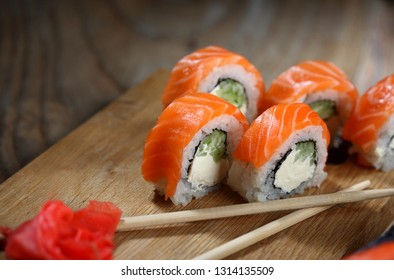 Philadelphia roll sushi with salmon, prawn, avocado, cream cheese. Sushi menu. Japanese food Closeup.Wooden background