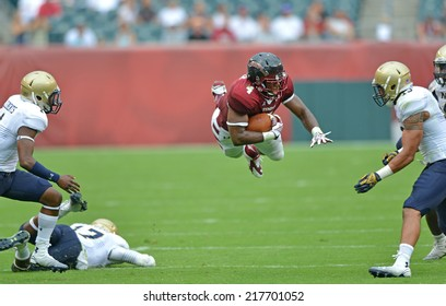 PHILADELPHIA - SEPTEMBER 6: Temple Owls running back Kenneth Harper #4 goes airborne after being hit during a NCAA football game between Temple and Navy September 6, 2014 in Philadelphia.