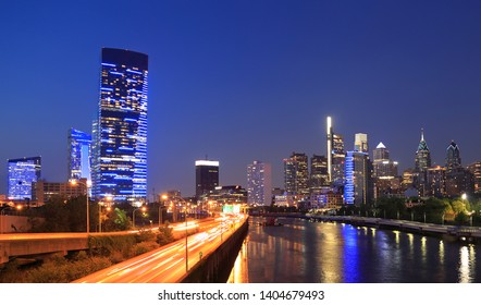 Philadelphia skyline at night with the Schuylkill River on the foreground