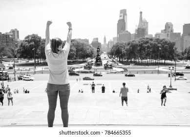 PHILADELPHIA, USA - JUNE 17, 2016: A female standing with her arms in the air on top of the Rocky steps  in Philadelphia.