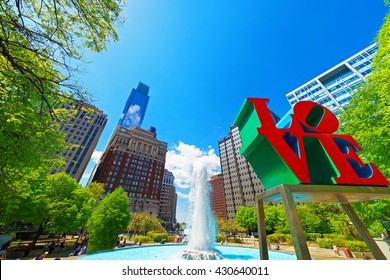 Philadelphia, USA - May 4, 2015: Love sculpture in the Love Park in Philadelphia, Pennsylvania, USA. Tourists in the park. Skyline with skyscrapers on the background