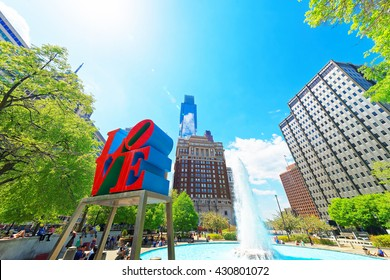 Philadelphia, USA - May 4, 2015: Love sculpture in Love Park in Philadelphia, Pennsylvania, USA. Tourists in the park. Skyline with skyscrapers on the background