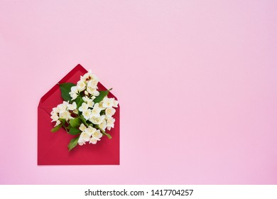 Philadelphus or mock-orange flowers in red envelope on pink pastel background. Flat lay of Birhday, Mothers Day, bachelorette, Wedding concept. Copy space, top view.