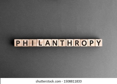 Philanthropy - word from wooden blocks with letters, to help poor people altruism charity philanthropy concept,  top view on grey background