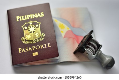 Philippine passport and rubber stamp on page of passport, white background.