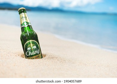 Philippines - Aug 2020: A bottle of Chang Beer partially buried in the sand by a tropical beach.