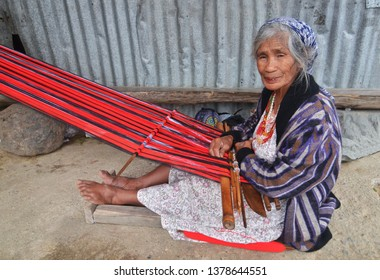 PHILIPPINES, BANAUE - MARCH 17, 2019: Old Philippine woman produces traditional clothing on loom in the Banaue