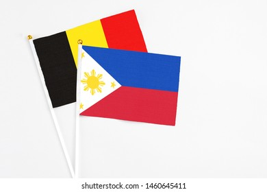 Philippines and Belgium stick flags on white background. High quality fabric, miniature national flag. Peaceful global concept.White floor for copy space.