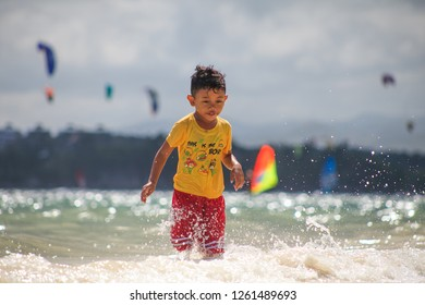 PHILIPPINES, BOARACAY - December 1 1918:  little asian kid running in the sea waters on the beach with kitesurfing spot on the background