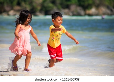 PHILIPPINES, BORACAY - December 1 1918: Asian philippino kids having fun playing on the seashore. Happy childhood. Boy and girl running in shallow water