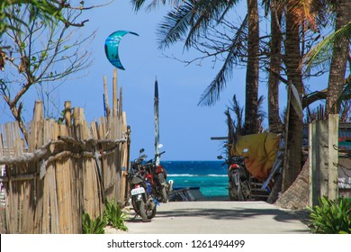 PHILIPPINES, BORACAY - December 1 1918:  typical domestic east asian street with bamboo fence and bikes and palms. BLue sea with flying kite on the background. Travel photography