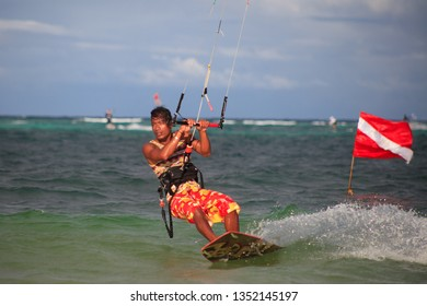 PHILIPPINES, BORACAY ISLAND, BULLABOG BEACH- January 01 2019: Kitesurfing guy edging upwind on his board. Water sports adventure