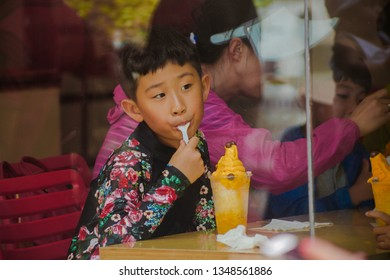 PHILIPPINES, BORACAY ISLAND, D-MALL - January 01 2019: Asian boy looking in the window, while enjoying his mango ice cream sweet craft dessert. Tourism