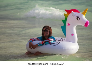 PHILIPPINES, BORACAY ISLAND, D-MALL - January 01 2019: Young asian girl swimming in the sea on the rainbow unicorn