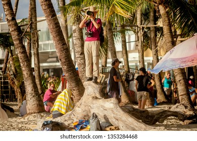 PHILIPPINES, BORACAY ISLAND, D-MALL - January 01 2019: Chinese tourist photographer taking pictures on the sunny beach