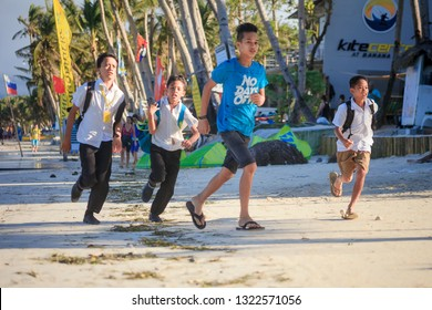 PHILIPPINES, BORACAY ISLAND - January 01 2019: After ending of lessons happy  asian school kids running home on Bulbog beach.