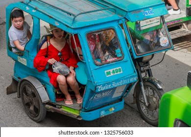 PHILIPPINES, BORACAY ISLAND - January 01 2019:  Beautiful chinese girl in red dress sitting in blue tricycle, popular philippino bike.