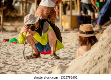PHILIPPINES, BORACAY ISLAND - January 01 2019: Chinese tourist taking portrait picture of his girlfriend on the beach