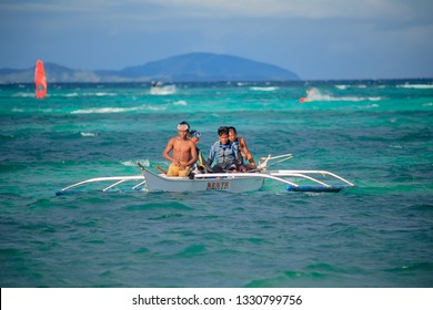 PHILIPPINES, BORACAY ISLAND  - January 01 2019: group of asian freedivers sitting in banka - traditional philippino wooden boat in beatyfull blue lagoon. Island life