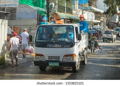 PHILIPPINES, BORACAY ISLAND- January 1, 2019: group of asian construction workers sitting in back of half truck
