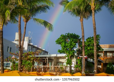 PHILIPPINES, BORACAY ISLAND, WHITE BEACH, FEBRUARY 14 2019: Rainbow in tropics above palms and beach resort.
