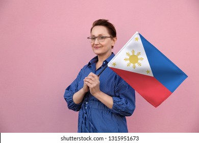 Philippines flag. Woman holding Philippine flag. Nice portrait of middle aged lady 40 50 years old holding a large flag over pink wall background on the street outdoors.